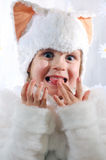 Happy kitten. Little girl wearing a white kitten costume licking her fingers Royalty Free Stock Photos