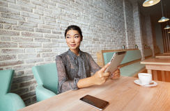 Happy Korean  female using touch pad during coffee break in restaurant. Smiling latin woman watching video on her digital tablet computer while sitting in modern Stock Images