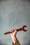 Happy Labor day concept. Senior man holding old metal wrench. Happy Labor day concept Stock Photos