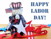 Happy Labor Day. Cute Uncle Sam figurine on wood table with red white and blue stars and ribbons isolated on white with removable Happy Labor Day message royalty free stock photography