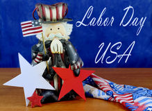 Happy Labor Day. Cute Uncle Sam figurine on wood table with red white and blue stars and ribbonswith blue background with removable Happy Labor Day message royalty free stock photo