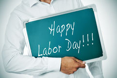 Happy labor day. A man holding a chalkboard with the sentence happy labor day written in it Royalty Free Stock Image