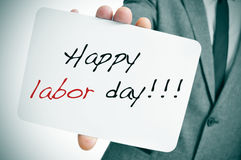 Happy labor day. A man wearing a suit showing a signboard with the text happy labor day written in it Stock Images