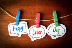 Happy Labor Day. Paper speech bubbles with text Happy Labor Day hanging on the line against dark wooden background Stock Image