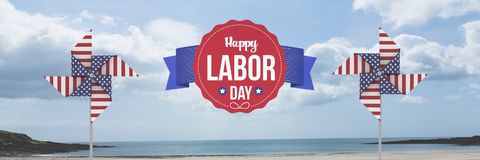 Happy labor day text and USA wind catchers in front of sea Stock Photography