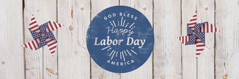 Happy labor day text and USA wind catchers in front of wood Stock Photography