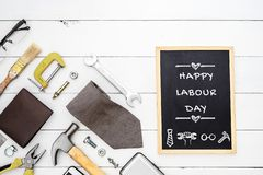 Happy Labour Day background concept. Flat lay of construction blue collar handy tools and white collar`s accessories over wooden royalty free stock photos