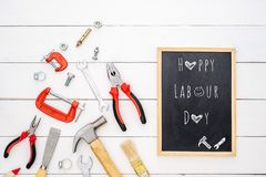 Happy Labour Day background concept. Flat lay of construction handy tools with black chalkboard with happy labour day text over. Wooden floor background royalty free stock photography