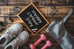 Happy Labour Day Fitness and healthy active lifestyle background concept. Training sneakers, dumbbells, sport bra and headphones. On wooden background aerobics royalty free stock photo