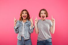 Happy ladies friends pointing to copyspace. Image of two happy ladies friends standing isolated over pink background. Looking camera pointing to copyspace Stock Photography