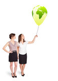 Happy ladies holding a green globe balloon Royalty Free Stock Images