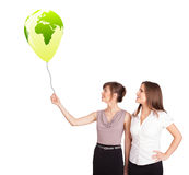 Happy ladies holding a green globe balloon Stock Image