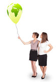 Happy ladies holding a green globe balloon Stock Photography