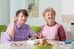 Happy ladies. Two happy senior ladies sitting together in lounge Royalty Free Stock Images