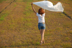 Happy lady. Asian young woman are very happy. She dancing on a field in the evening sunshine and waving her scarf in the wind royalty free stock images