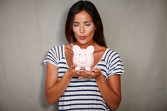 Happy lady blow kissing a piggy bank with savings Royalty Free Stock Photography