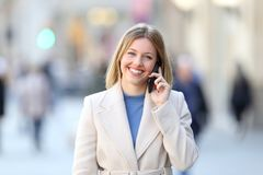 Happy lady calling on phone and looking at camera. Front view portrait of a happy lady calling on phone and looking at camera on the street in winter Stock Photos