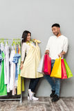 Happy lady choosing clothes near man holding shopping bags. Stock Photography