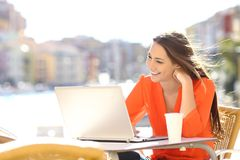 Happy lady in a coffee shop terrace uses a laptop. In a coast town street royalty free stock images