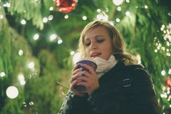 Happy lady with cup of coffee against christmas tree. Happy young lady with cup of coffee against illuminated christmas tree, shallow depth of field stock photography