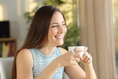 Happy lady drinks coffee looking away royalty free stock photography