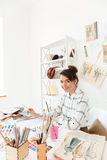 Happy lady fashion illustrator drawing. Picture of young happy lady fashion illustrator sitting at the table and drawing. Looking at camera stock photography