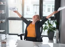 Outgoing businesswoman rising arms up. Happy lady flourishing arms while sitting at table. She keeping documents in hands. Achievement concept stock photography