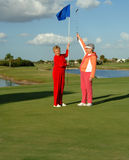 Happy lady golfers celebrate. Two senior women hold up flag and putter on the putting green of a golf course Stock Photography