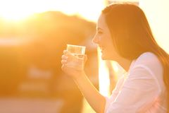Happy lady holding a glass of water at sunset Royalty Free Stock Photos