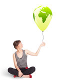 Happy lady holding a green globe balloon Stock Images