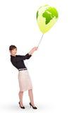 Happy lady holding a green globe balloon Royalty Free Stock Photos