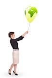 Happy lady holding a green globe balloon Stock Photography