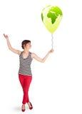 Happy lady holding a green globe balloon Royalty Free Stock Photography