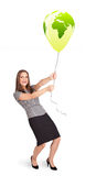Happy lady holding a green globe balloon Stock Photos