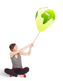 Happy lady holding a green globe balloon Stock Photos