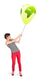 Happy lady holding a green globe balloon Royalty Free Stock Image