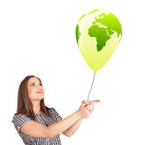 Happy lady holding a green globe balloon Stock Photo