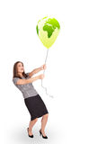 Happy lady holding a green globe balloon Stock Photography