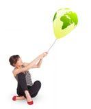 Happy lady holding a green globe balloon Royalty Free Stock Image