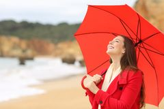 Happy lady holding umbrella in winter breathing. Happy lady holding red umbrella in winter breathing fresh air on the beach stock photo