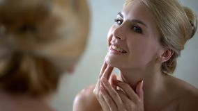 Happy lady looking at mirror, pure healthy and smooth skin, anti-aging treatment royalty free stock image