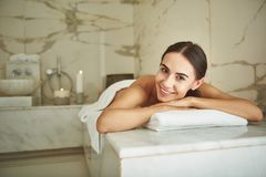 Happy lady looking at you and smiling while lying in hammam royalty free stock photo