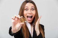Happy lady with opened mouth looking camera and holding golden bitcoin isolated Royalty Free Stock Images