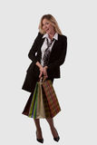 Happy lady shopper. Full body of an attractive blond woman in a skirt business attire smiling and holding in some shopping bags over white royalty free stock photography