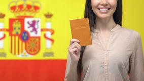 Happy lady showing passport, standing against Spanish flag, getting citizenship. Stock footage stock footage