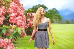 Happy lady stands ping bush flowers enjoy. Happy lady stands near bush with pink flowers and enjoys royalty free stock images