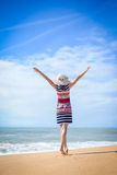 Happy lady in striped dress reaching up to blue Royalty Free Stock Images