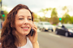 Happy lady talking on mobile phone walking on a street. Happy young lady talking on mobile phone walking on a street stock photo