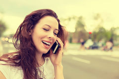 Happy lady talking on mobile phone walking on a street. Happy young lady talking on mobile phone walking on a street royalty free stock photos