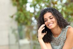 Happy lady talking on phone sitting in a park royalty free stock images